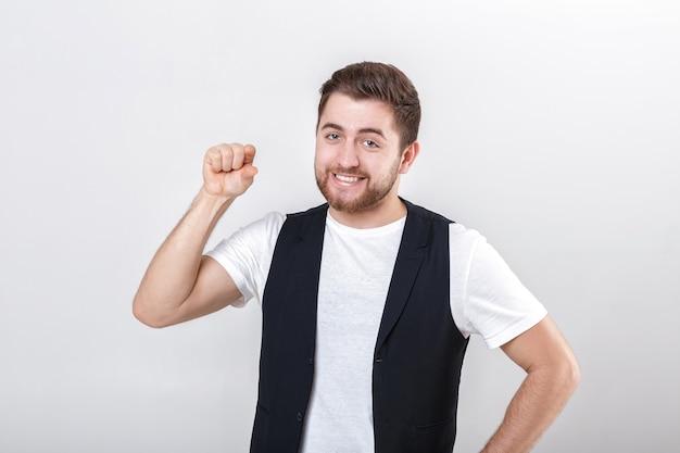 Jonge knappe man met een baard in een wit overhemd en een zwart vest toont het gebaar van kloppen