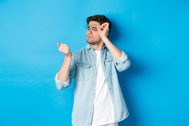 Jonge knappe man met een bril die naar zijn vingernagels kijkt, manicure controleert, over blauwe achtergrond staat