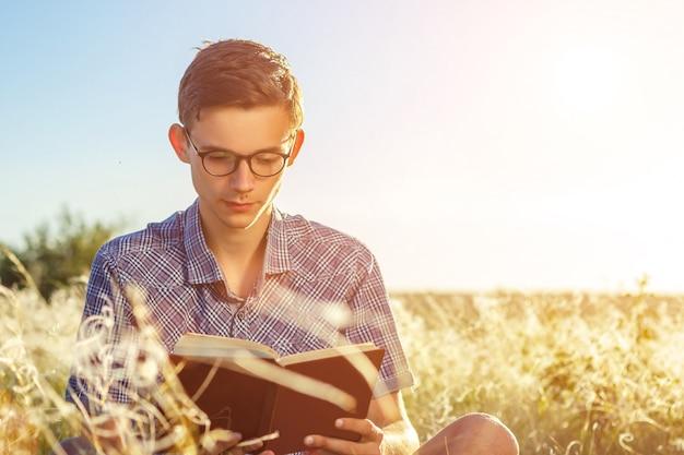 Jonge knappe man met een bril lezen van een boek met een bril op een zonnige dag.