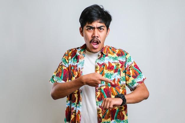 Jonge knappe man met een casual shirt over een geïsoleerde witte achtergrond in haast wijzend om naar de tijd te kijken, ongeduld, overstuur en boos vanwege vertraging van de deadline