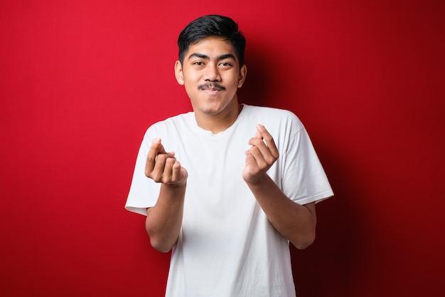 Jonge knappe man met een casual shirt over een rode achtergrond die geldgebaar doet met handen, om salarisbetaling vraagt, miljonairszaken