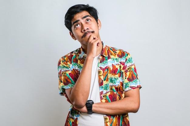 Jonge knappe man met een casual shirt over een witte achtergrond denkend bezorgd over een vraag, bezorgd en nerveus met de hand op de kin