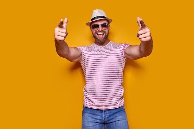 Jonge knappe man met een casual t-shirt over een geïsoleerde gele achtergrond wijzend met de vinger...