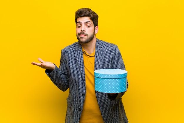 Jonge knappe man met een doos tegen oranje achtergrond