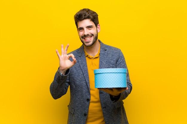 Jonge knappe man met een doos tegen sinaasappel