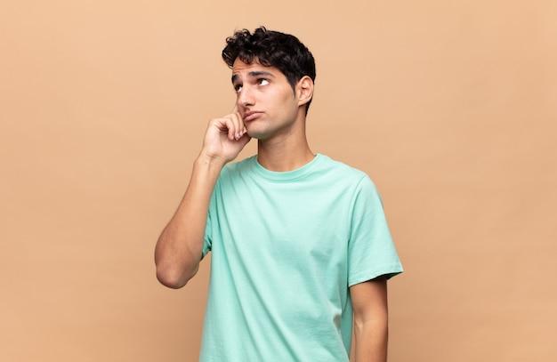 Jonge knappe man met een geconcentreerde blik, zich afvragend met een twijfelachtige uitdrukking, opkijkend en opzij