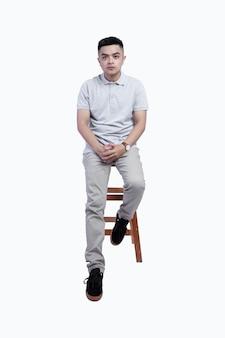 Jonge knappe man met een grijs gemêleerd poloshirt poseerde in een stoel