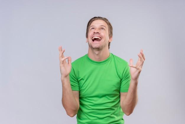 Jonge knappe man met een groen t-shirt, gek blij met opgeheven armen die over witte muur staan 3