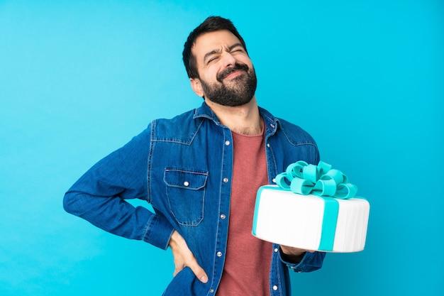 Jonge knappe man met een grote cake die lijdt aan rugpijn omdat hij zich heeft ingespannen
