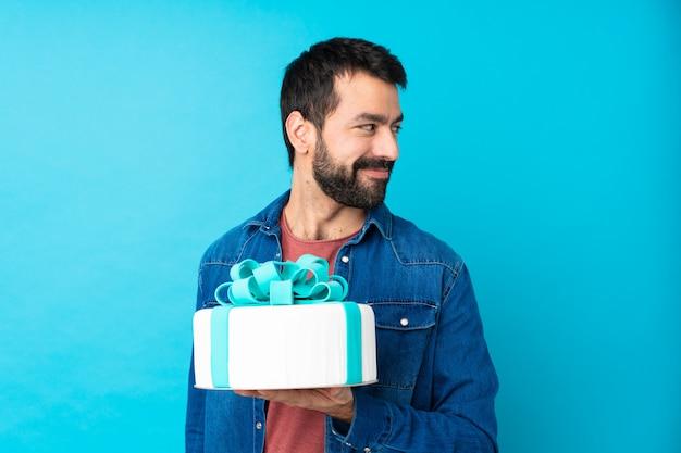 Jonge knappe man met een grote cake over geïsoleerde blauwe muur met gekruiste en gelukkige wapens