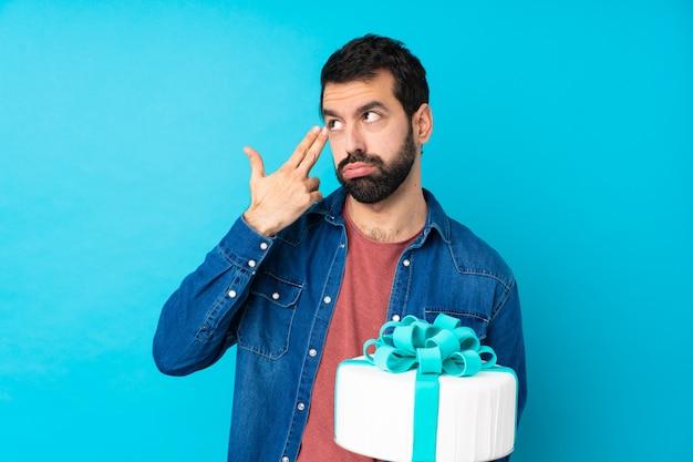 Jonge knappe man met een grote cake over geïsoleerde blauwe muur met problemen die zelfmoordgebaar maken