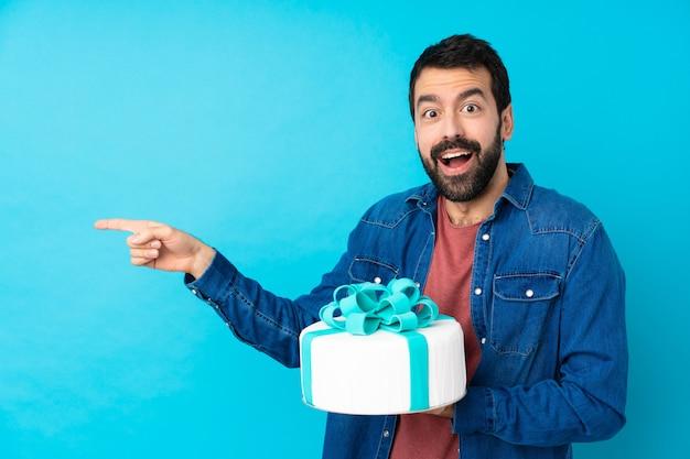 Jonge knappe man met een grote cake verrast en wijzend kant