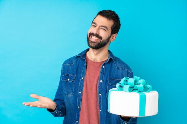 Jonge knappe man met een grote taart over geïsoleerde blauwe muur glimlachen