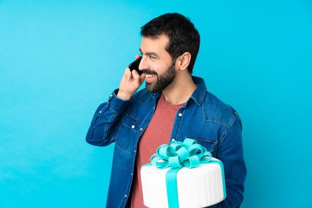 Jonge knappe man met een grote taart over geïsoleerde blauwe muur houden van een gesprek met de mobiele telefoon met iemand