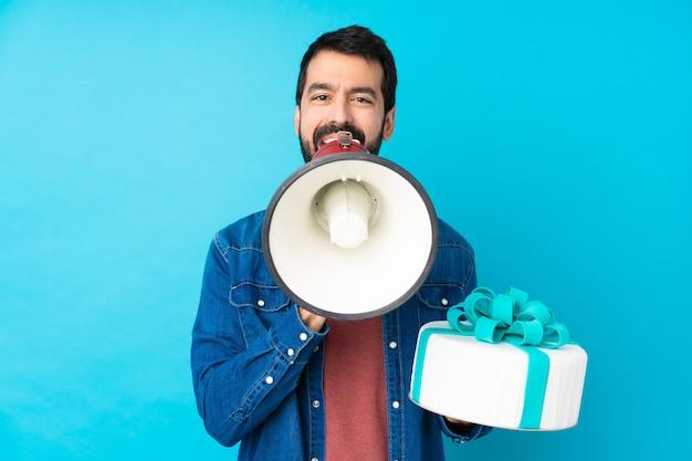 Jonge knappe man met een grote taart over geïsoleerde blauwe muur schreeuwen door een megafoon