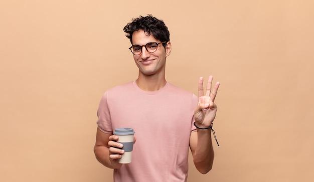 Jonge knappe man met een koffie die en vriendelijk glimlacht kijkt, nummer twee of seconde met vooruit hand toont, aftellend