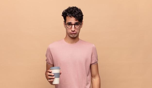 Jonge knappe man met een koffie die verdrietig en zeurderig is met een ongelukkige blik, huilend met een negatieve en gefrustreerde houding