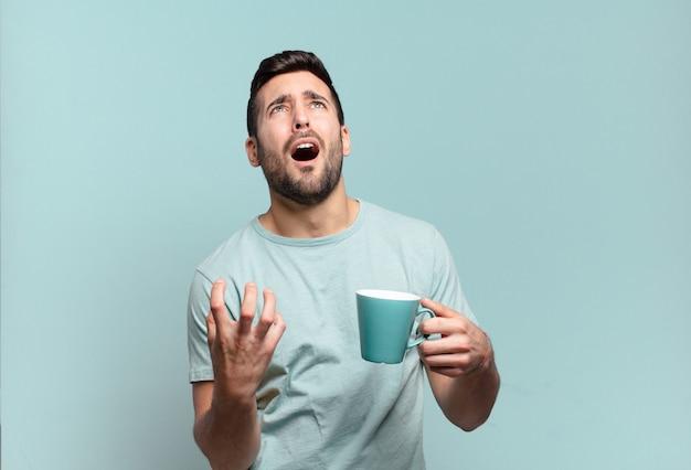 Jonge knappe man met een koffiekopje