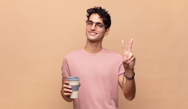 Jonge knappe man met een kopje koffie glimlachend en kijkt gelukkig, zorgeloos en positief, gebaren overwinning of vrede met één hand