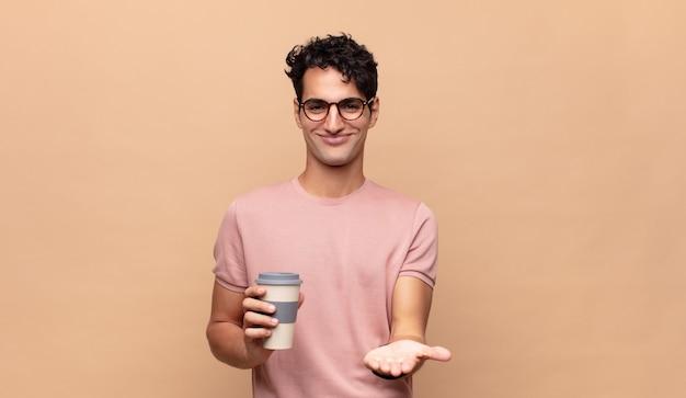 Jonge knappe man met een kopje koffie glimlachend gelukkig met vriendelijke, zelfverzekerde, positieve blik, aanbieden en tonen van een object of concept