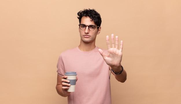 Jonge knappe man met een kopje koffie op zoek ernstig, streng, ontevreden en boos met open palm stop gebaar maken