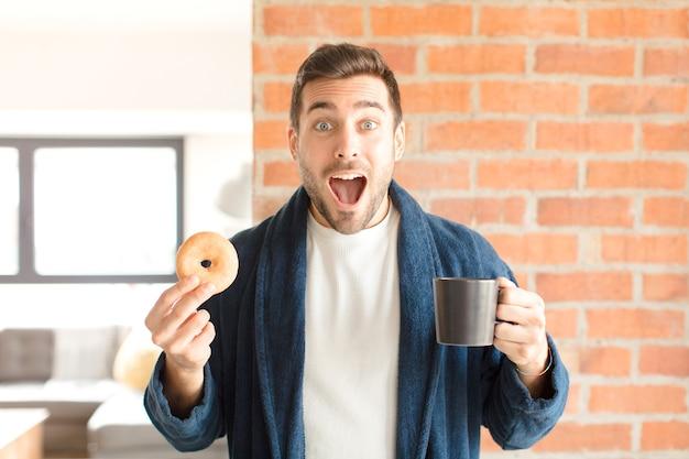 Jonge knappe man met een kopje koffie thuis
