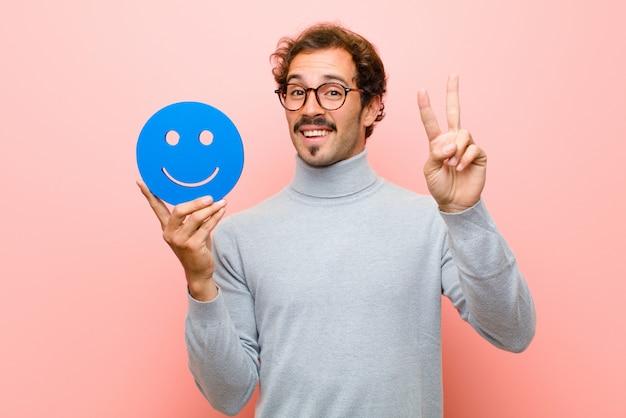 Jonge knappe man met een lachend gezicht tegen roze platte muur
