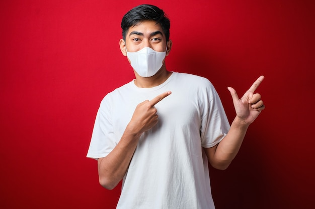 Jonge knappe man met een medisch masker glimlachend en kijkend naar de camera wijzend met één handen en vingers naar de zijkant over rode achtergrond