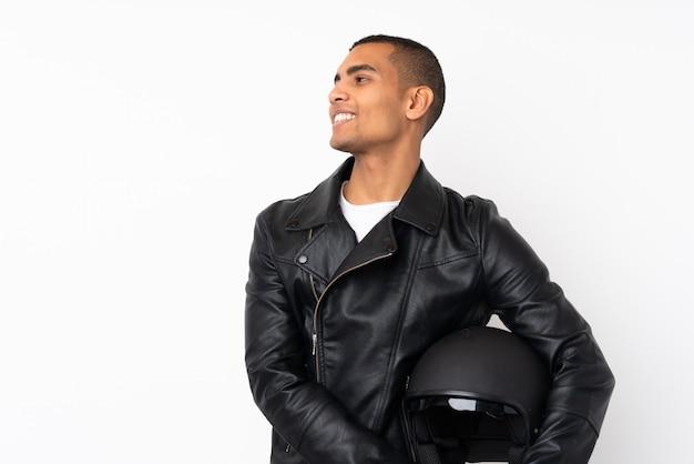 Jonge knappe man met een motorhelm over geïsoleerde witte muur op zoek naar de kant