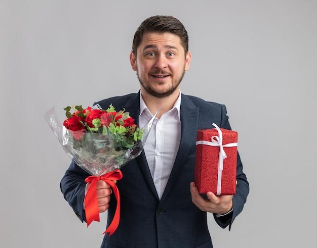 Jonge knappe man met een pak met een boeket rozen en een cadeautje voor valentijnsdag met een blij gezicht dat vrolijk lacht over een witte muur