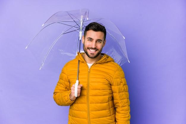 Jonge knappe man met een paraplu blij, glimlachen en vrolijk.