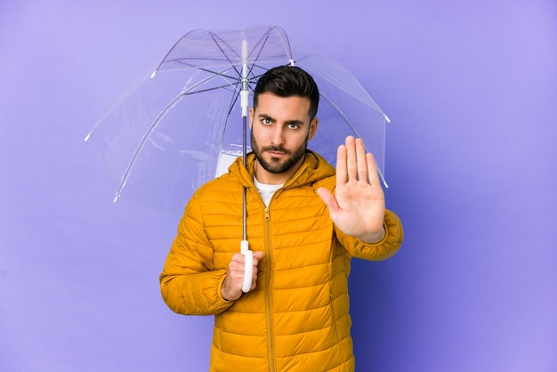 Jonge knappe man met een paraplu geïsoleerd staande met uitgestrekte hand die stopbord toont, waardoor je wordt voorkomen.