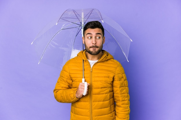 Jonge knappe man met een paraplu geïsoleerd verward, twijfelachtig en onzeker.