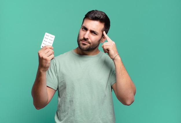 Jonge knappe man met een pillentablet. ziekte of pijn concept