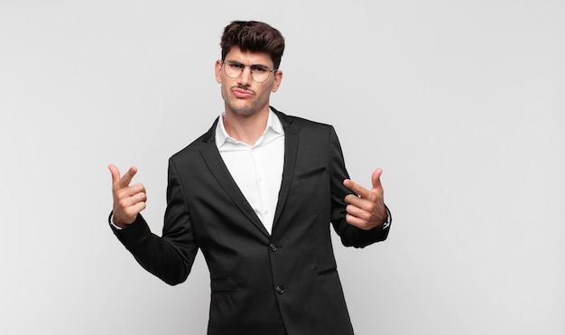 Jonge knappe man met een slechte houding die er trots uitziet, naar boven wijst of een leuk teken maakt met handen