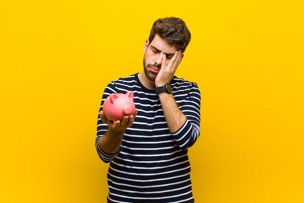 Jonge knappe man met een spaarvarken