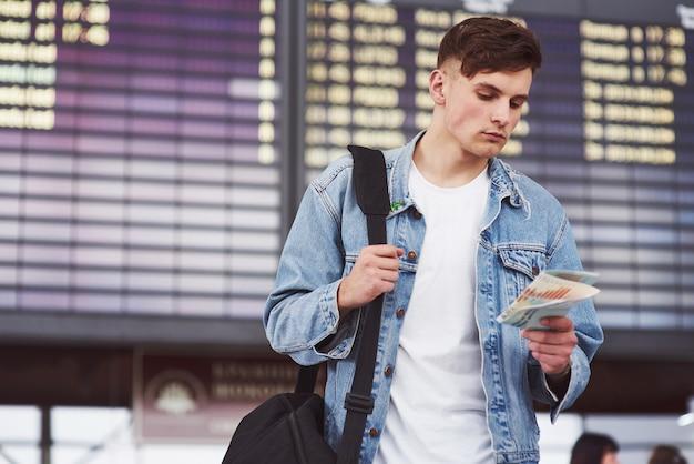 Jonge knappe man met een tas op zijn schouder haast zich naar het vliegveld.