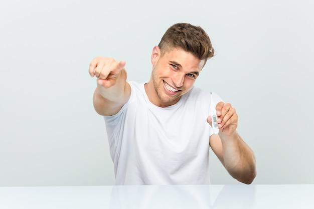 Jonge knappe man met een thermometer vrolijke glimlach wijzend naar de voorkant.