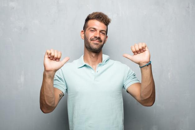 Jonge knappe man met een trotse, gelukkige en zelfverzekerde expressie
