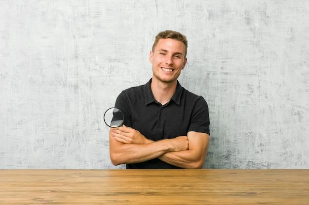 Jonge knappe man met een vergrootglas glimlachen vol vertrouwen met gekruiste armen.