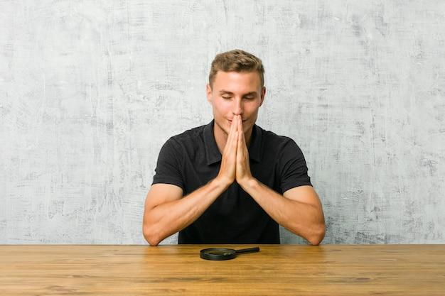 Jonge knappe man met een vergrootglas hand in hand bidden in de buurt van de mond, voelt zich zelfverzekerd.