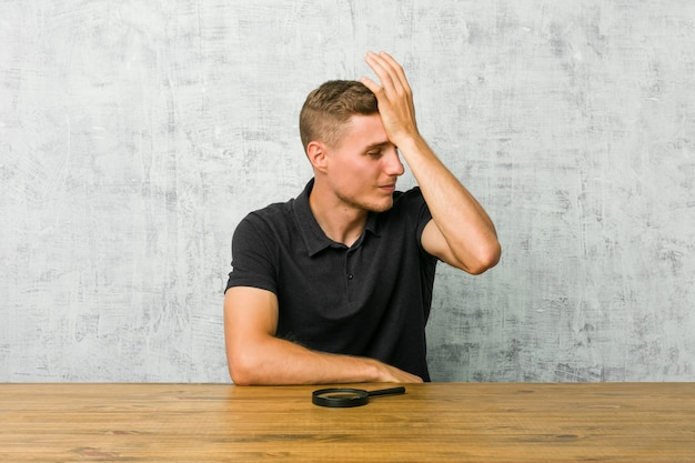 Jonge knappe man met een vergrootglas iets vergeten, voorhoofd met palm meppen en ogen sluiten.