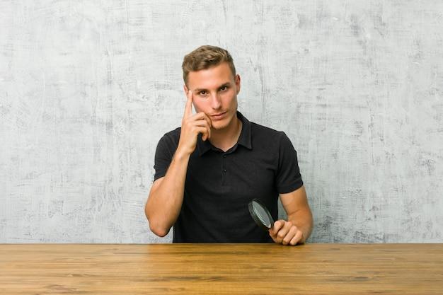 Jonge knappe man met een vergrootglas wijzende tempel met vinger, denken, gericht op een taak.