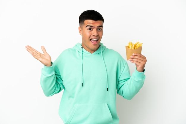 Jonge knappe man met gefrituurde chips over geïsoleerde witte achtergrond met geschokte gezichtsuitdrukking