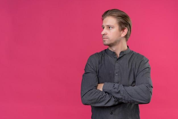 Jonge knappe man met gekruiste armen opzij kijken met ernstig gezicht staande over roze muur