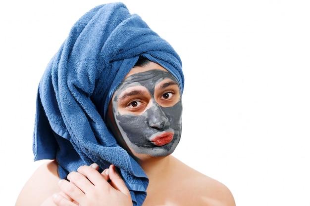 Jonge knappe man met gezichtsmasker als een vrouw, geïsoleerd