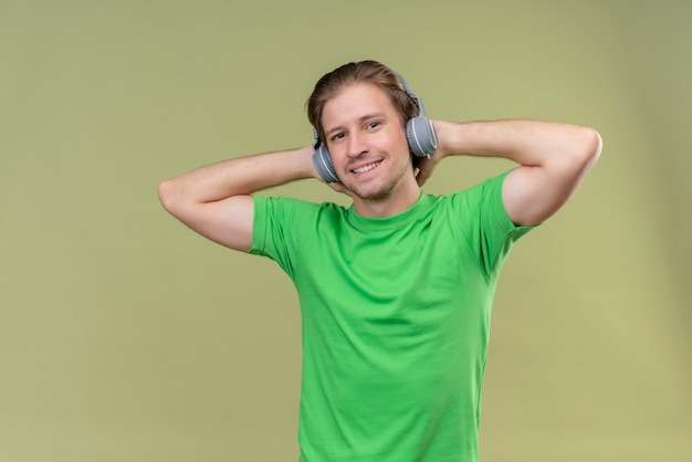 Jonge knappe man met groen t-shirt met koptelefoon genieten van favoriete muziek staande over groene muur