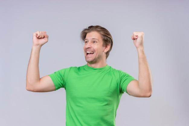 Jonge knappe man met groen t-shirt, opgewonden en blij, gebalde vuisten
