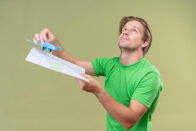 Jonge knappe man met groene t-shirt bedrijf speelgoed vliegtuig en kaart glimlachend staande over groene muur opzoeken