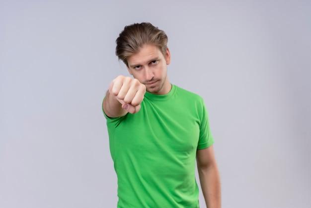 Jonge knappe man met groene t-shirt gebalde vuist die zich uitstrekt naar de camera met ernstig gezicht staande over een witte muur